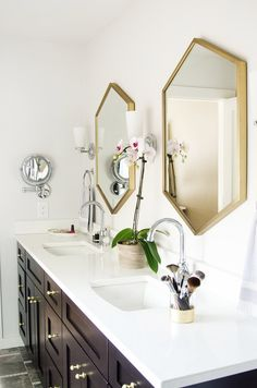 dark vanity with brass West Elm mirrors and Restoration Hardware sconces