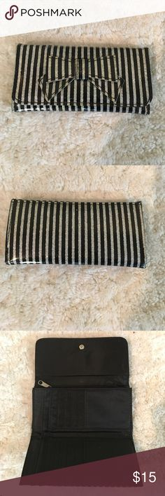 Cute wallet! Black and silver stripes wallet with bow. Lots of compartments, and a convenient zipper for change. Approx 6 inches wide, and 3 inches long when closed. Almost 10 inches long when opened. Good condition Bags Wallets