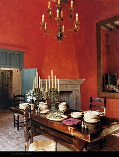 Such a shocking, gorgeous brick red dining room. The slate blue trim works with the color, enhancing it, and the white dishes glow.