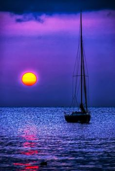 sail boat on blue water in a sunset of pink, gold and red.