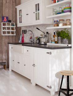 Mit diesen Möbeln können Sie Ihre eigene Landhausküche gestalten. Wir   bieten Ihnen eine Spüle mit viel Stauraum, einen Oberschrank mit Türen, ein offenes Wandregal sowie Unterschränke mit links oder rechts   angeschlagener Tür an. Die Türbeschläge ähneln alten Kühlschrankgriffen. Alle Möbel sind aus massiver Kiefer und sind weiß gestrichen. Die Arbeitsfläche ist schieferfarben mit einer wasserfesten Farbe gestrichen. Das Spülbecken ist aus Porzellan.