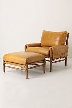 **RHYS CHAIR $2498.00  **RHYS OTTOMAN $998.**Mid century modern-inspired take on the club chair is sure to become an instant classic. Perched atop a handcrafted solid beech frame, its cushy padding is covered in slick, lager-hued leather that buckles at the sides like a valise.