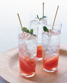 Grapefruit-and-Mint Mojito | A simple mint syrup takes the place of crushed leaves in this grapefruit-mint mojito. Be sure to add fresh sprigs on top for a dash of color and heady aroma. Tall, slender glasses and long stirring sticks impart a modern elegance.
