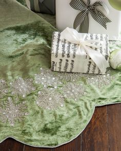 The Sage Velvet Snowflake Tree Skirt features a lovely velvet fabric, hand-applied snowflakes with glass beads, and delicate silver cording on the edges.