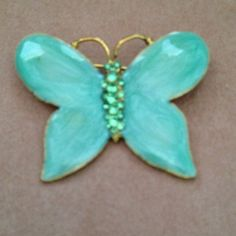 Teal butterfly pin w/ bling Edges and antennae are gold tone trim. Color of wings are light teal, not quite blue, not quite green. Body is twinkling light teal bling. Beautiful. Like new. Jewelry Brooches