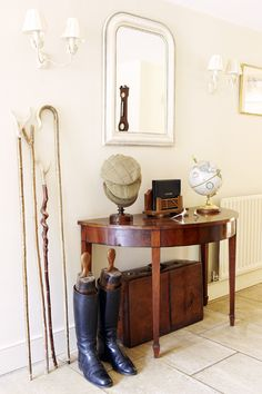 Antique furniture in a hallway is combined with a vintage suitcase, riding boots, walking sticks and tweed caps,
