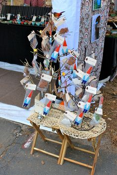 Metal tree on a small table, placed at front of booth: very appealing.  Art, display, and photo by Tasha McKelvey