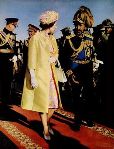 Queen Elizabeth walking on a red carpet in Addis Ababa with the Conquering Lion of Judah, Emperor Haile Selassie. They are followed by Prince Phillip and Selassie's Lion Crown Prince Asfa Wassan. She was the first British Monarch to visit Ethiopia