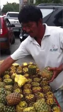 This man cutting a pineapple