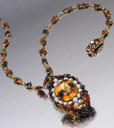 An Arts and Crafts gold, citrine quartz, pearl and enamel pendant-necklace, Tiffany & Co., circa 1910. Designed by Louis Comfort Tiffany, the elongated oval pendant set in the centre with a cushion-shaped faceted citrine surrounded by clusters of pearls, within a frame of purple grape clusters and leaves enamelled in Autumn hues of orange, gold and green, supported on a chain necklace, the links of similar design to the pendant, signed Tiffany & Co. #LouisComfort #Tiffany #ArtsAndCrafts