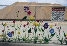 Crocheted flowers on a construction fence by The Ladies Fancywork Society in downtown Denver.
