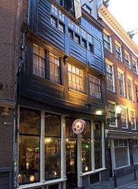 Dit houten huis aan de Zeedijk is gebouwd in 1550 en is 1 van de 2 laatste originele houten huizen in Amsterdam. In de 17e eeuw verbrasten veel zeelieden al hun geld, zodat zij hun rekeningen niet meer konden betalen. De eigenaar van de herberg In den Aepjen, vroeg een van zijn klanten om een aapje voor hem mee te nemen, om zijn schuld te vereffenen. Andere zeelieden brachten ook aapjes mee, tot de herberg vol aapjes zat … en vlooien. De uitdrukking 'in de aap gelogeerd' komt hier vandaan.