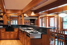 Arts & Crafts Style: A House Remade  by Patricia Poore. The open kitchen presents a finished side with circulation flow outside the work space. Custom details include soapstone, a built-in crepe cooker, and a bar for serving and sitting.