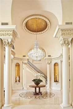 Exquisite foyer is enhanced with faux gilding,dramatic crystal chandelier,elaborate dome ceiling. Soaring 20  foot ceiling,Corinthian columns,vaulted arches with faux bronze dore decoration. Marble inlay imported from Iran is the centerpiece of room.