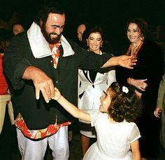 Italian Tenor Luciano Pavarotti dances with a Lebanese girl upon his arrival at Beirut airport 10 June 1999, while Nazik Hariri wife of former prime minister Rafic Hariri and actress Nidal Ashkar look at them.