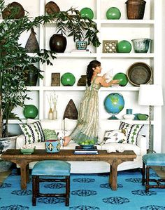 Gorgeous turquoise and emerald green offset by white shelving & sofa. #decorateyourspace