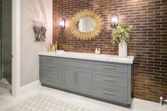 A metallic brown tile accent wall serves as a beautiful backdrop for the rich gray vanity in this contemporary bathroom. A gold starburst mirror complements the vanity hardware, and a marble countertop adds an elegant touch. Tile Accent Wall, Wall Tiles, Newport Beach, Vanity Countertop, Transitional House, Transitional Lighting, Beach House Decor, Grey Walls, Home And Family