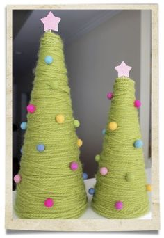 Styrofoam cones wrapped in yarn with pom poms glued on. Sounds easy! So cute, and I love that I could use the muted/alternative Christmas colors