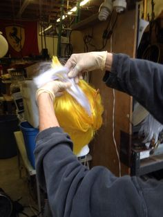 7. Positioning glued in added section to yellow wig, then spraying with varnish and clipping into place until dry.
