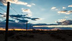 A static timelapse with a slow pan across a typical Karoo farm landscape with a sheep fence in the foreground as the sun sets behind dramatic clouds, dip to a black silhouette. Sheep Fence, Blue Sky Clouds, Sun Sets, Black Silhouette, Windmill, Geology, Stock Footage, South Africa, Dip