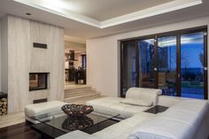 Large modern white leather L-shaped sectional sofa here fills this cozy living space over dark wood flooring, with pass-through fireplace and large black and glass coffee table.