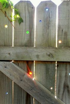 Insert marbles into holes drilled in a wooden fence