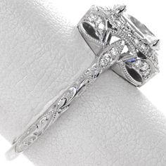Design 3266 - Antique inspiration and elegance are intertwined in this haloed 1.00 carat oval cut design. Micro pavé, graceful scroll engraving and milgrain detail adorn the band for a vintage appeal. The basket features a tapestry of arched diamonds and two marquise surprise diamonds.