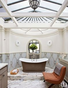 Formerly a conservatory, Veronica Toub's skylit bath features a Bisazza-tile wainscot designed to resemble button-tufted fabric; the tub is by Waterworks, with Volevatch fittings