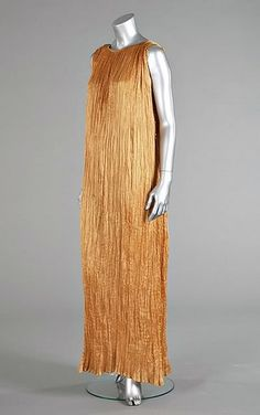 Mariano Fortuny, Delphos dress. Golden apricot pleated silk, the armholes and sides adorned with striped Murano glass beads.
