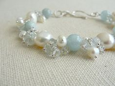 This gorgeous bracelet features smooth round aquamarine stones and white baroque pearls. They are wire wrapped in sterling silver and interspersed with clusters of small aquamarine stones and freshwater pearls.