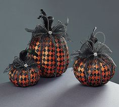 Add some glam to your Fall celebrations with these pumpkins covers with black and orange fabric in a harlequin pattern. The fabric is covered over foam. The pumpkins are covered in tulle, mesh and emb