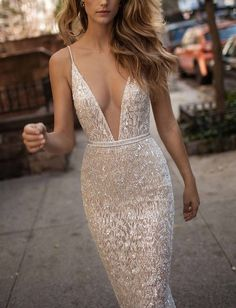 Cut with a daring plunging neckline and curve-flaunting silhouette, a meticulously beaded mermaid gown stuns in more ways than one.