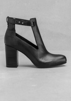 Leather ankle boots featuring cut-outs, a croco-embossed heel and an edgy cufflink-closure for the delicate ankle strap.