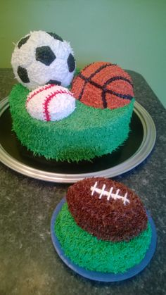 "Sports Ball 1st Birthday Party! 12"" round cake base with Wilton ball mold for soccer ball, half mold for basketball, and a baseball cupcake mold for the baseball. All frosting is piped butter cream. Smash cake is a 6"" round topped with two football shaped cupcake molds stacked and carved to make an actual football. Football was half green and gold cake and half orange and blue...dad is a Packers fan and mom is a Bears fan."