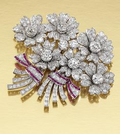 RUBY AND DIAMOND DOUBLE CLIP BROOCH, 1940S.  Each designed as a tied bunch of flowers, set throughout with circular-, single-cut and cushion-shaped diamonds, the ribbons embellished with calibré-cut rubies, fitted case by Wartski Ltd, 138 Regent Street, London W.1