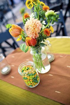 Green and orange flower arrangement in jars along with sweets.