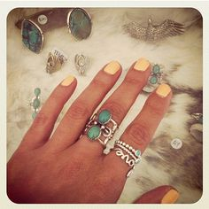 soft yellow polish and ring candy. Would love to sport the The Coyote Turquoise Finger Cuff she has on her middle finger.