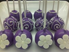 Vanilla cake pops dipped in coloured white chocolate and decorated with edible pearls, white chocolate and fondant flowers.