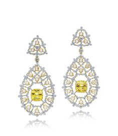 A PAIR OF 4.70 AND 4.56 CARAT YELLOW SAPPHIRE AND DIAMOND EAR PENDANTS. Each suspending a cushion-shaped yellow sapphire, within a two-tier diamond surround, to the diamond set surmount, mounted in 18K gold.