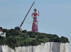 A huge statue of Theresa May flicking the V sign has been erected on the White Cliffs of Dover in a bizarre stunt.