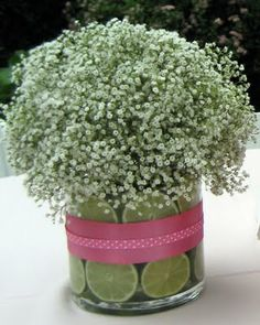 Simple, yet would look nice on each guest table!  Simply cut up fruit (oranges, limes, or lemons work especially well!) for the bottom and place large bouquets of baby's breath flowers inside!  Wrap with a ribbon in your colors for the finishing touch!