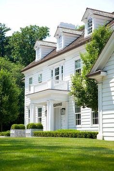 White house, horizontal wood siding, porch over entry, repetitive gables