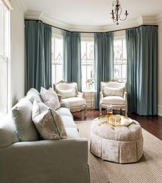 Blue and grey living room features a bay window dressed in blue curtains filled with a pair of French chairs and a round brass and marble table. Chic living room boasts a gray linen skirted sofa adorned with beige flocked pillows with teal piping facing a light brown velvet skirted ottoman atop a jute rug.