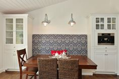 Love the fabric on the seat on the banquette, mismatched chair, built in cabinets surrounding it, and the barn lights.