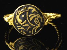 Extremely rare gold saxon ring with a flat circular bezel engraved with a champlevé zoomorphic pattern inlaid with black niello, displaying a fantastic beast, the sinuous body shown in profile with only two legs visible, Y-shaped paws, turned-back head, biting it's own tail. The hoop is formed by a single wire twisted like a torque, a typical early saxon design, the shoulders terminating in foliate motifs. England, Northumbria (?), probably late 9th century