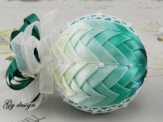 This ornament is made with cotton lace in two section and shiny satin ribbons placed on a styrofoam ball by technique pineapple and kimekomi. Created