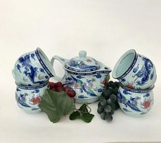 Dragon teapot set matching tea bowls set of 4  blue hue / red dragons hallmarked Chinese  teapot:  4 1/2 inch height  6 1/2 inch handle to spout  3 inch base  tea bowl set of 4:  2 1/2 inch height  with infuser  excellent condition  https://www.etsy.com/shop/CoCoBlueTreasures