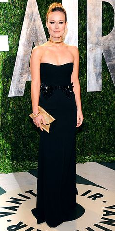 Olivia Wilde in a black strapless gown with leather accents at the hips, plus a collar choker, gold chain-embellished Salvatore Ferragamo clutch and Jimmy Choo sandals.