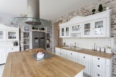This kitchen adds interest by incorporating various textures such as brick, tile and wood.  The refrigerator is uniquely located within a niche in the brick wall.
