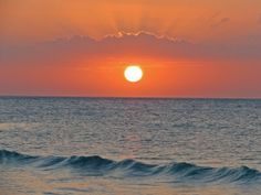 The sun sets against a vibrant peach sky over the Gulf of Mexico, in Isla Holbox.